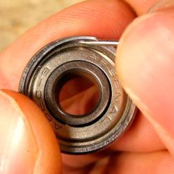 Öppna kullagret genom att pilla bort stålringen som spänner fast skölden